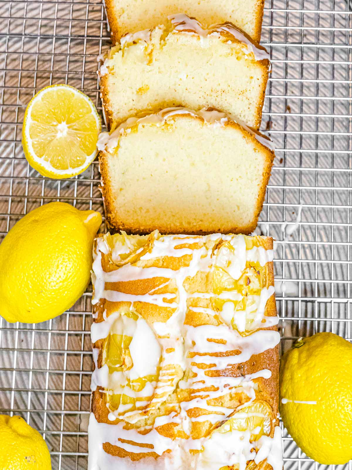 overhead of glazed lemon pound cake with slices on a cooling rack