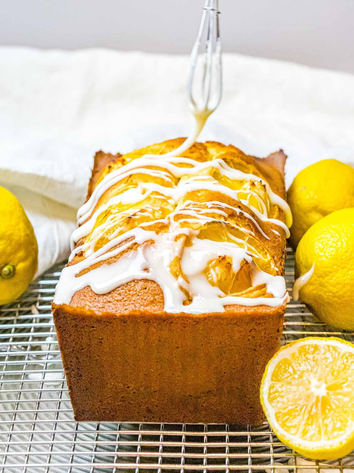 lemon pound cake being glazed with icing with a small whisk