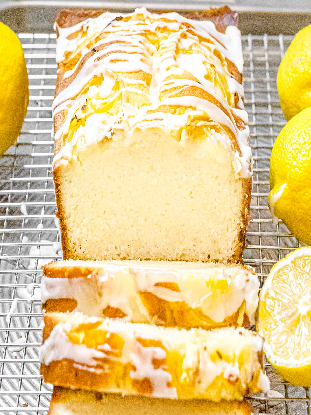 cross section of lemon pound cake with glaze drizzled on top next to lemons on a cooling rack