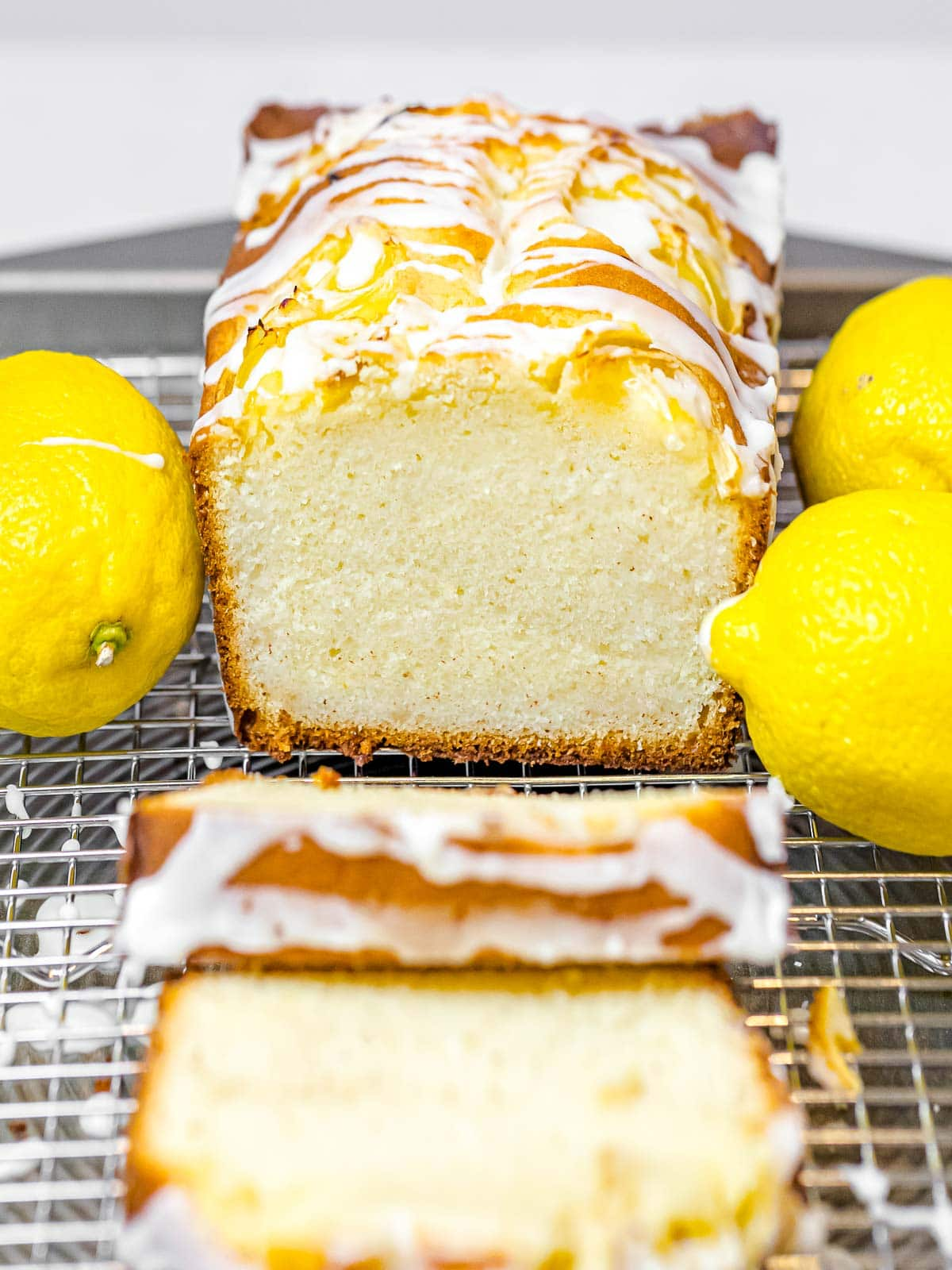 lemon pound cake glazed with icing with a golden brown crust sliced open next to lemons