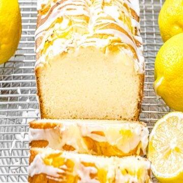 lemon pound cake with glaze sliced open next to lemons on a wire rack
