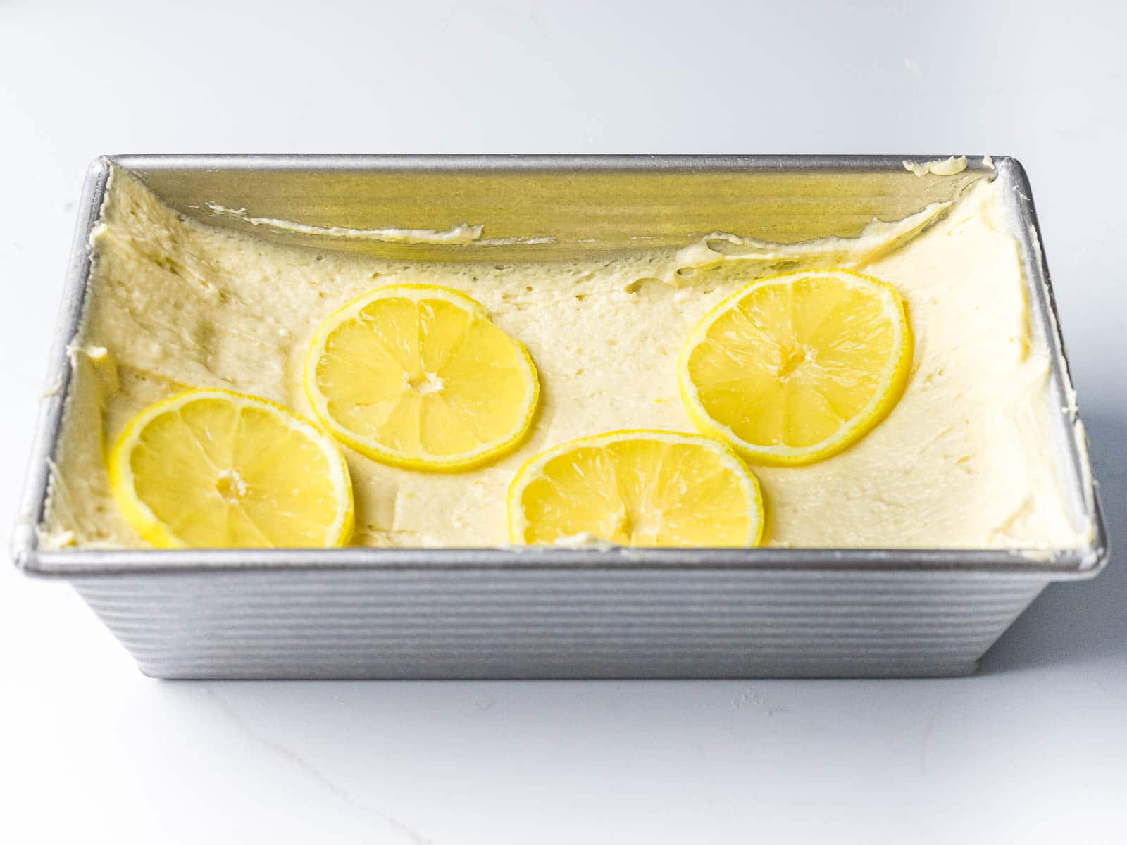pound cake batter made into a well topped with thin lemon slices in a metal loaf pan