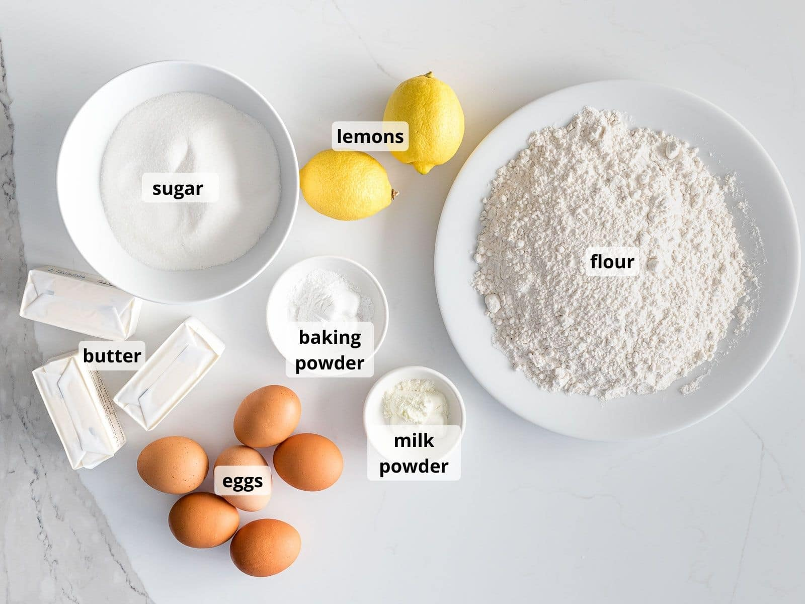 labeled ingredients for lemon pound cake in white bowls on a white background
