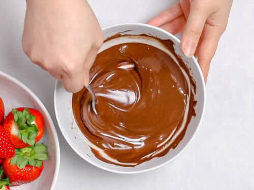 melted dark chocolate being stirred by a spoon in a white bowl next to a bowl of strawberries