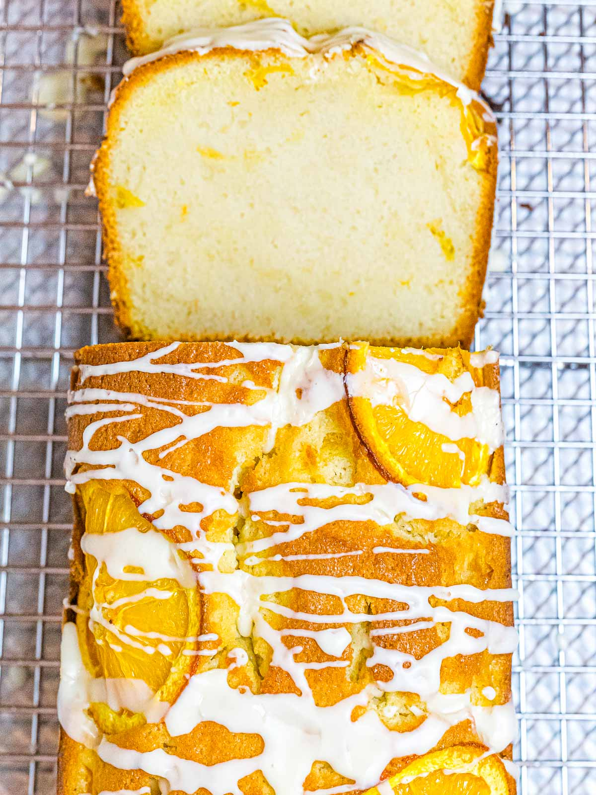 orange pound cake with glaze drizzled on top and decorated with orange slices