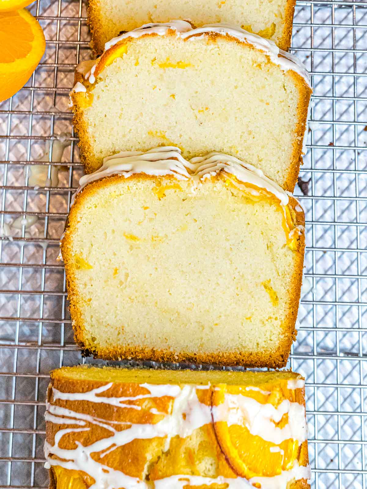 slices of orange pound cake covered in icing on top of a wire rack