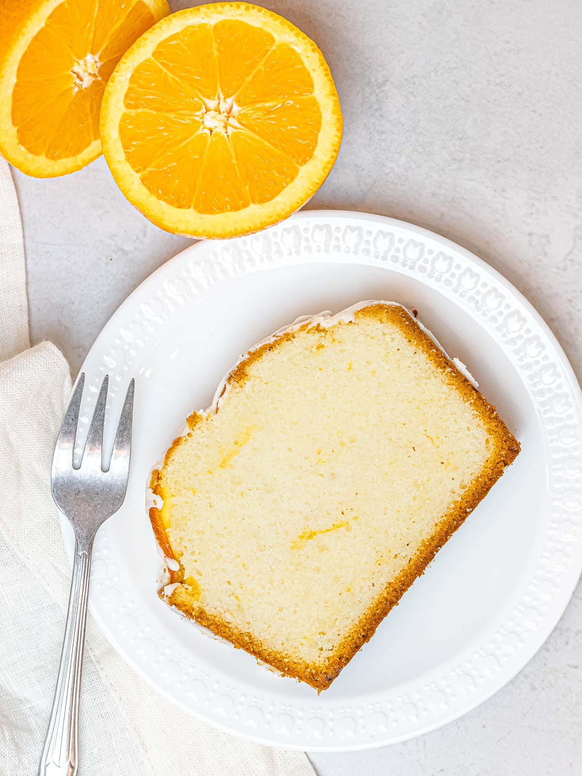 a slice of orange pound cake on a white plate with a fork next to oranges