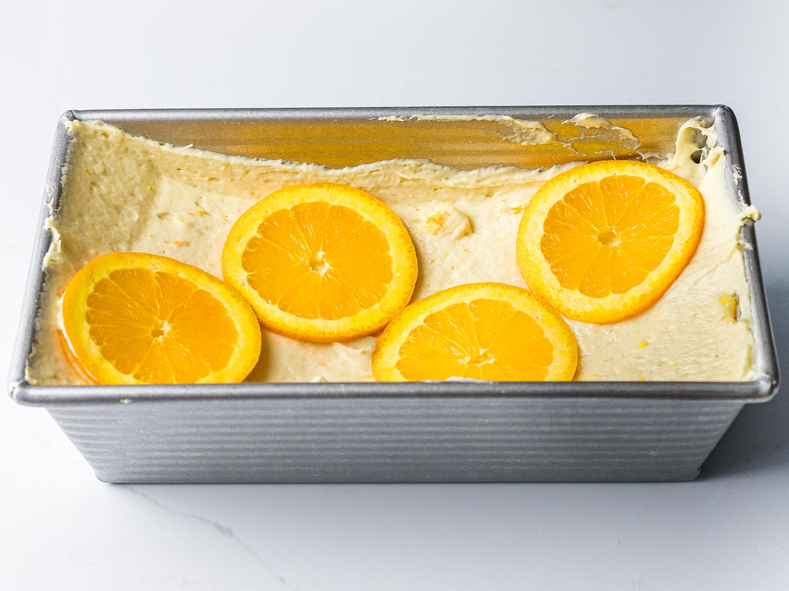 orange pound cake batter in a loaf pan with a well in the center with orange slices placed on top