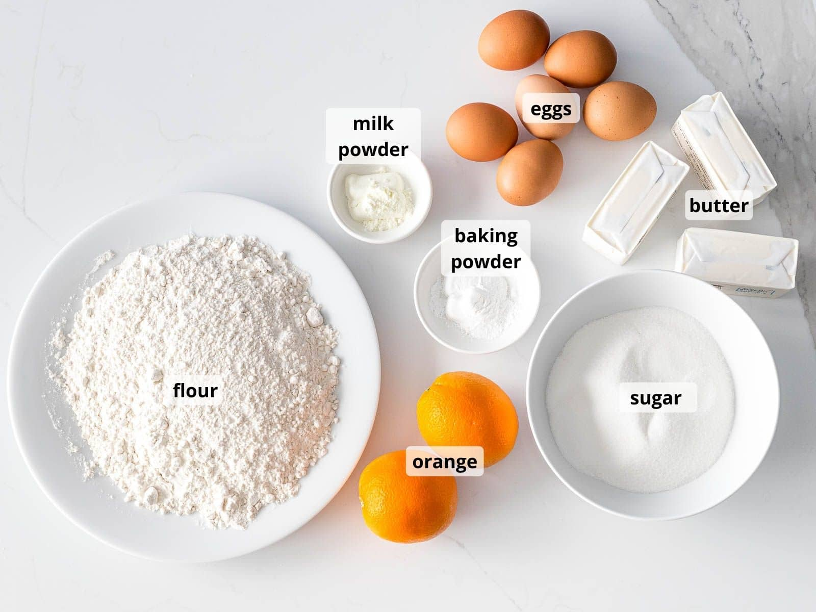 labeled ingredients for orange pound cake in small white bowls
