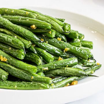 close up of stir fried Asian green beans on a white plate