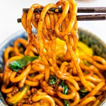 close up of stir fried yaki udon noodles held with chopsticks