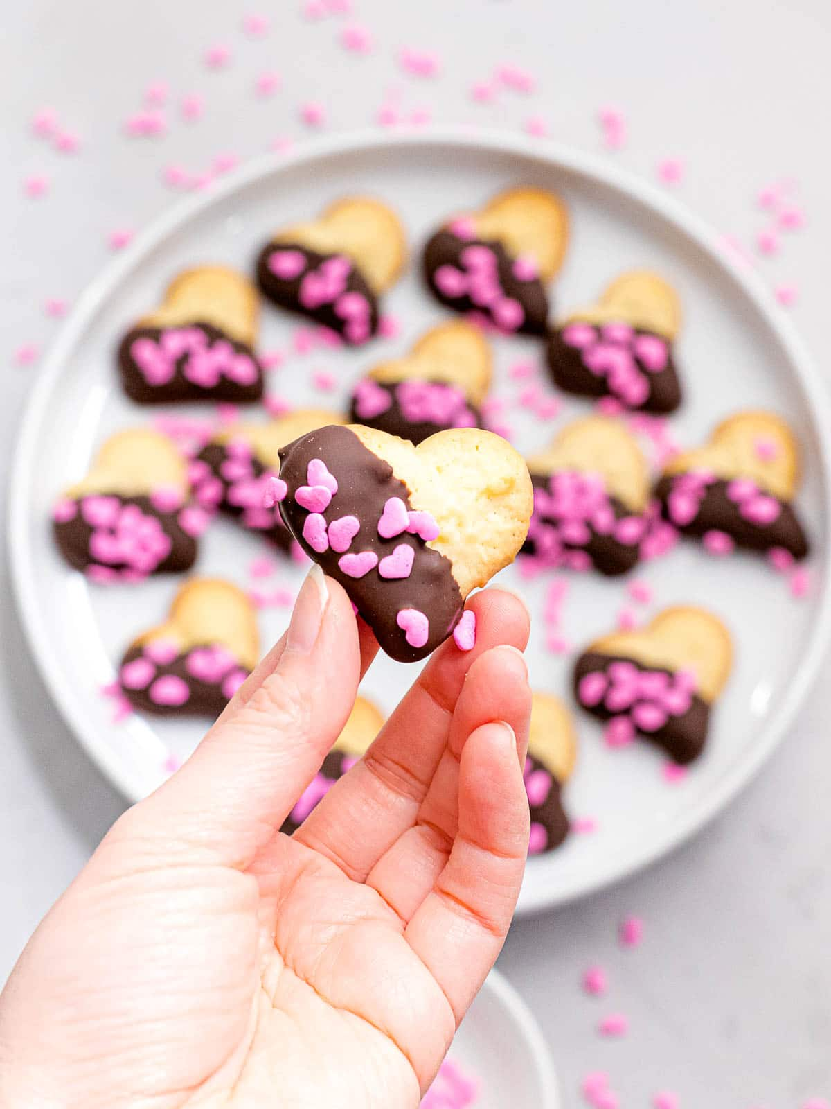 hand holding heart shaped Valentines day spritz cookie dipped in dark chocolate and decorated with pink sprinkles