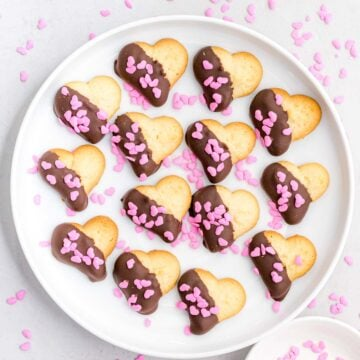 heart cookies dipped in dark chocolate decorated with pink heart shaped sprinkles laying on a white plate
