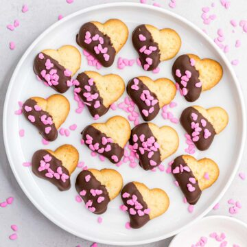 heart cookies dipped in dark chocolate decorated with pink sprinkles laying on a white plate