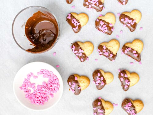 chocolate dipped heart cookies decorated with pink Valentine sprinkles next to melted chocolate and bowl full of pink heart shaped sprinkles