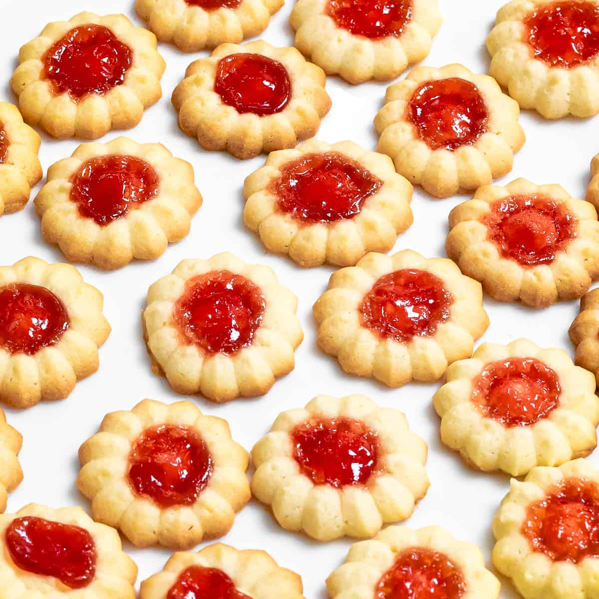 close up of jam thumbprint cookies made with a spritz cookie press and filled with strawberry jam