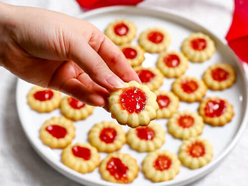 Close up of a jam thumbprint cookie held by a hand above a plate full of more jam cookies.
