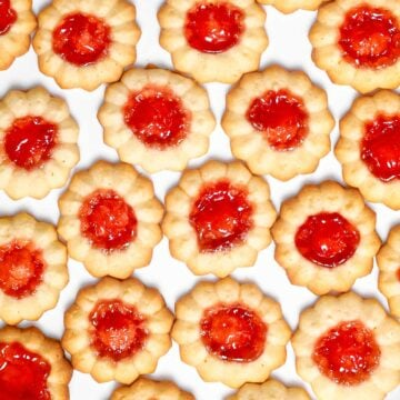 A close up of jam thumbprint cookies filled with red jam on a white surface.