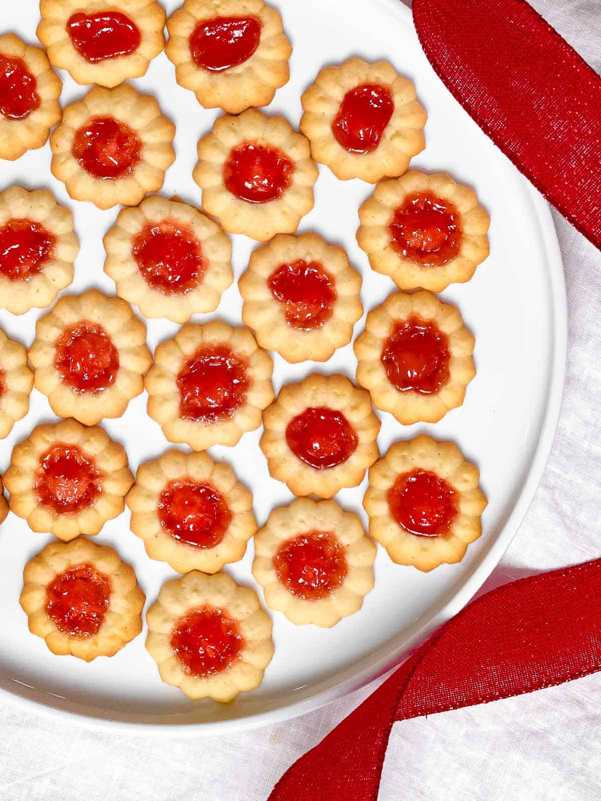 An overhead photo of jam thumbprint cookies filled with red jam in a white plate next to a red ribbon.