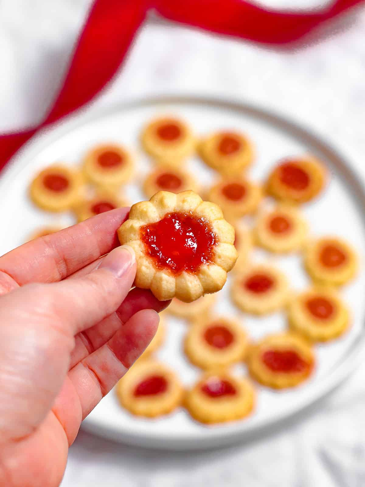 A hand holding a jam cookie filled with red strawberry jam with a plate full of jam cookies in the background.