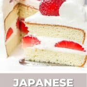 A slice of Japanese strawberry sponge cake decorated with fresh strawberries and whipped cream.