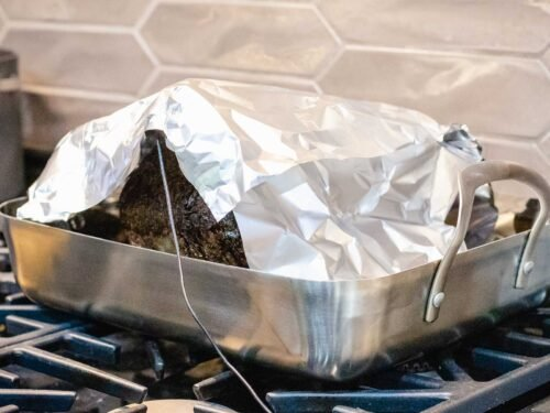 Standing rib roast resting on a roasting pan with a meat thermometer inserted and covered with foil.
