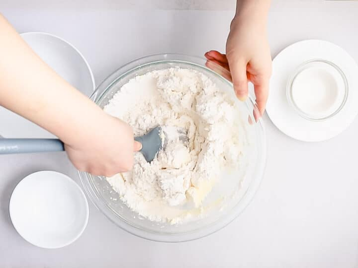 spritz cookie dough batter being folded with flour in a glass bowl with a grey spatula