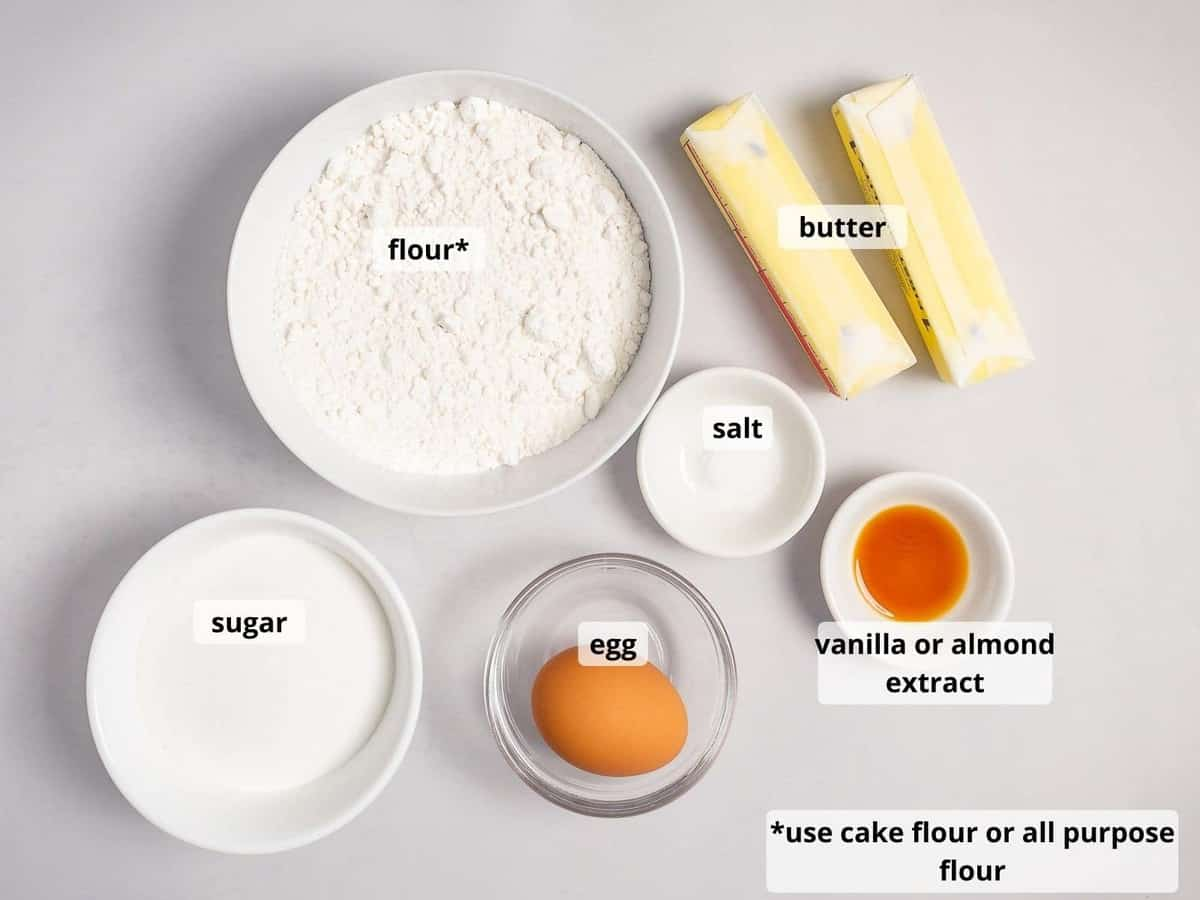ingredients for spritz cookies in small white bowls on a light background
