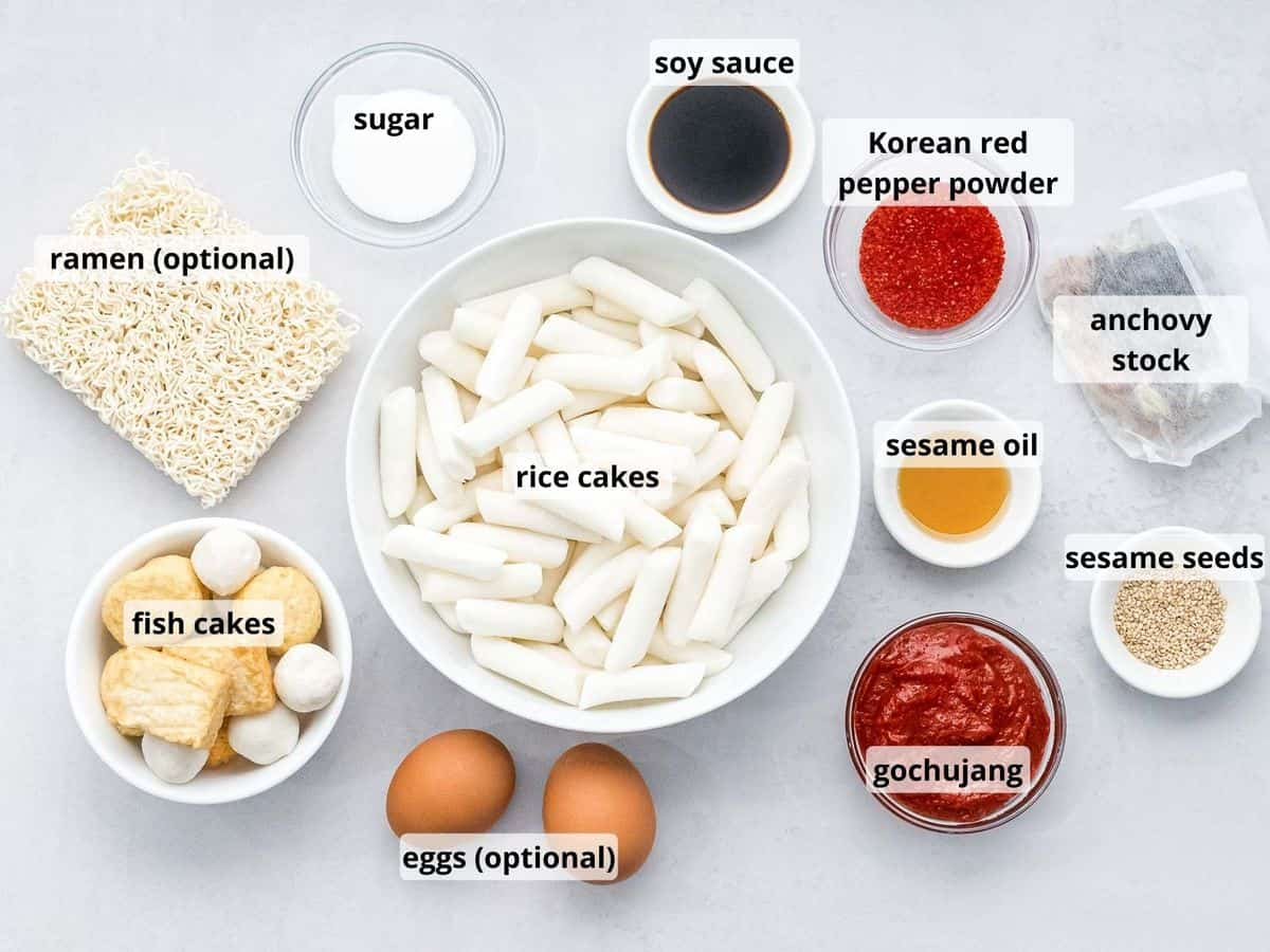 ingredients for tteokbokki with text overlay including rice cakes, gochujang, fish cakes, ramen, and eggs