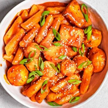 tteokbokki with fish cakes and eggs garnished with sesame seeds and scallions in a white bowl