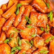 Tteokbokki made with Korean rice cakes and fish cakes in a spicy gochujang sauce in a white bowl.