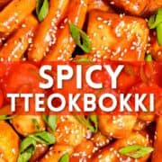 bowl of spicy tteokbokki with fish cakes, scallions, and sesame seeds with text overlay
