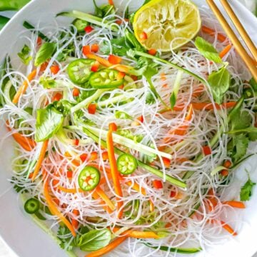 Vietnamese noodle salad with vermicelli rice noodles, lime, basil, vegetables, and dressing in a white bowl with chopsticks.