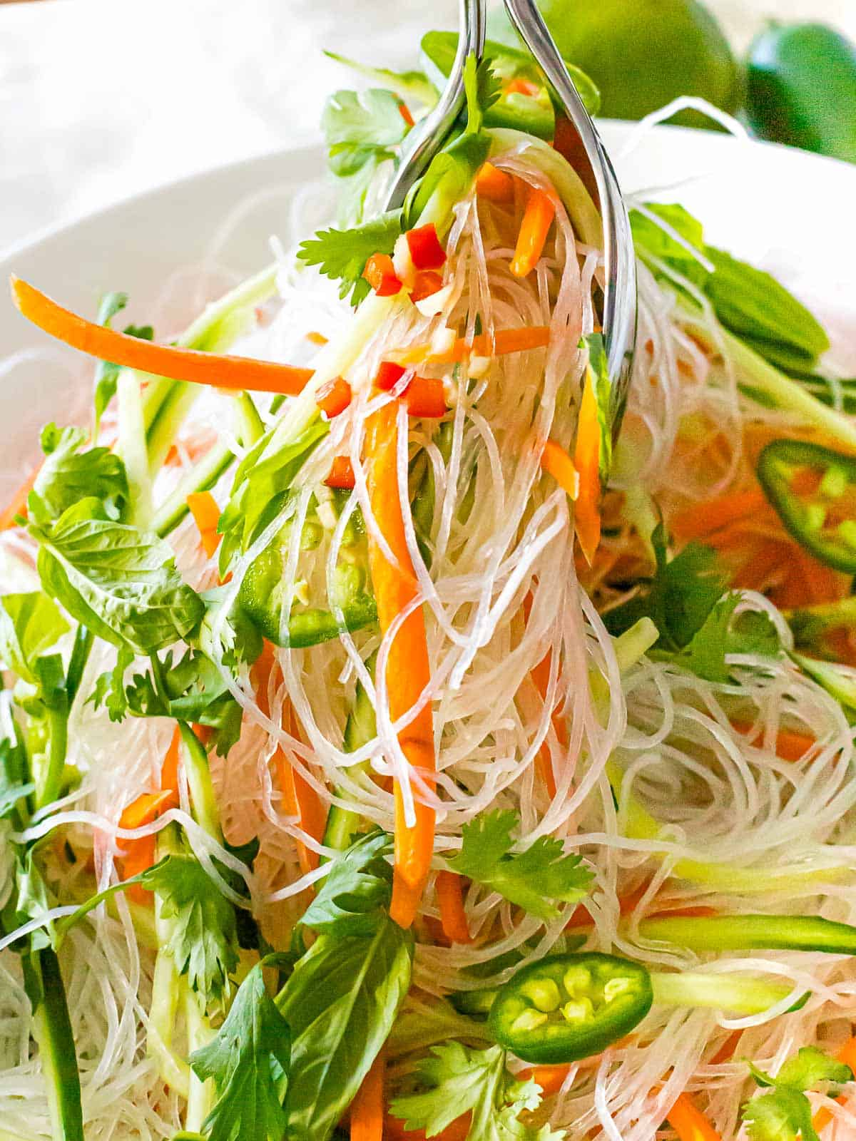 Vietnamese noodle salad with vermicelli rice noodles, basil, cilantro, carrots, and green peppers being lifted from a white bowl.