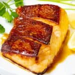 Chilean sea bass pan seared with golden brown crispy skin in an Asian marinade on a white plate with herbs and lemon.