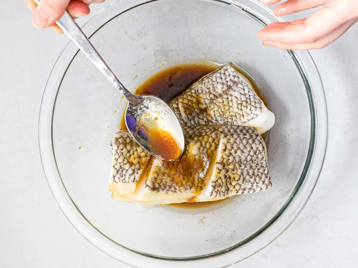 Two pieces of sea bass filet in a glass bowl with a soy marinade being spooned over it.