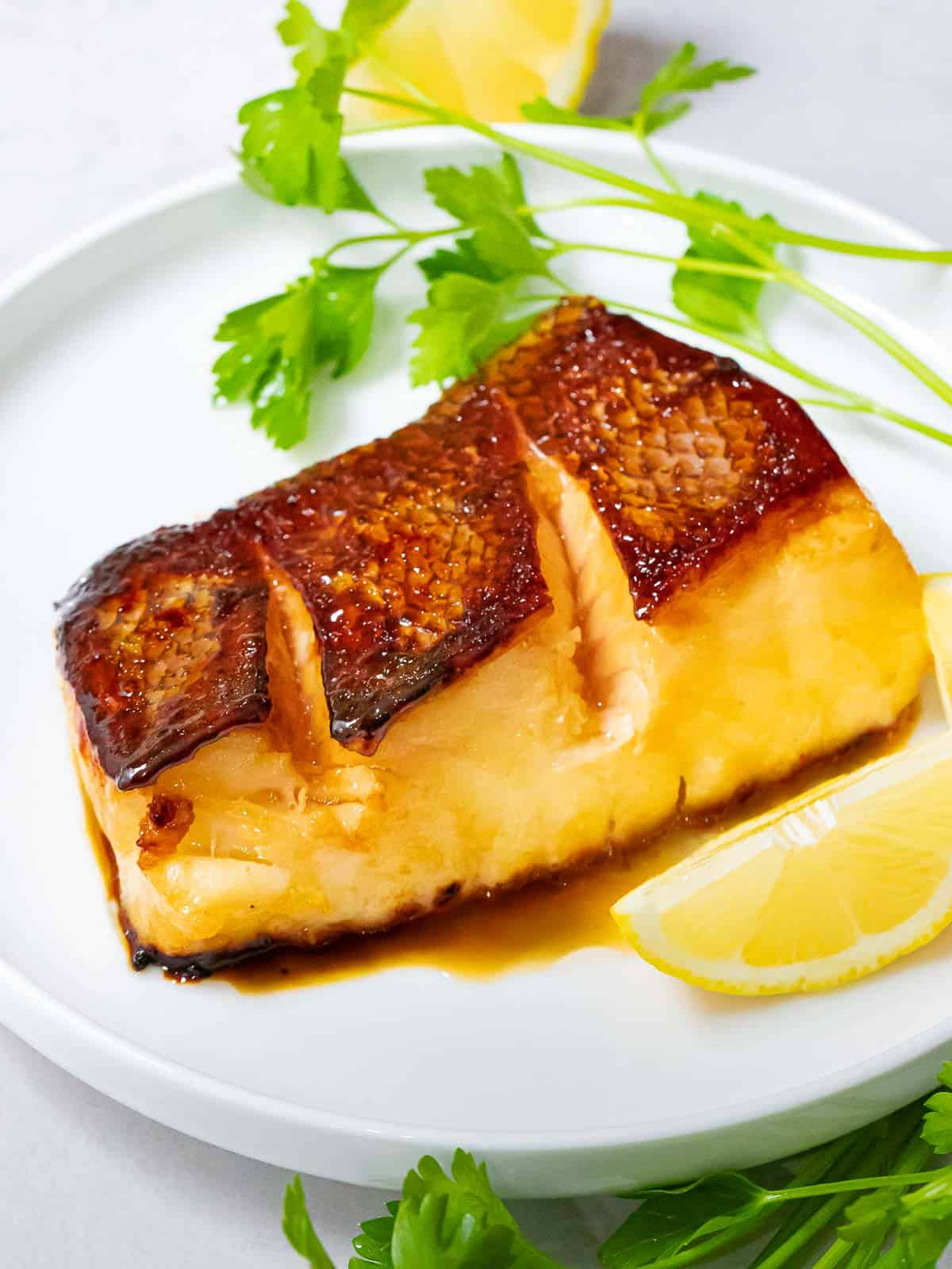 Chilean sea bass with crispy, golden brown skin marinated in Asian soy ginger marinade on a white plate next to lemon and parsley.