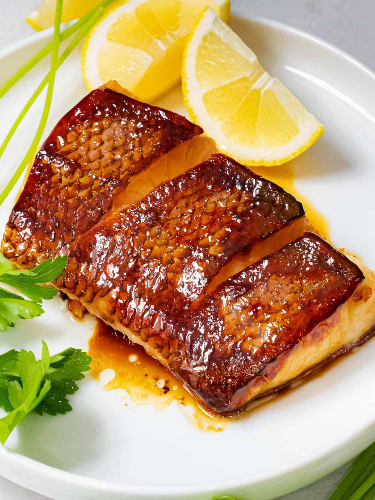 Close up of Chilean sea bass with crispy, golden brown skin with a soy ginger marinade on a white plate next to lemon wedges.