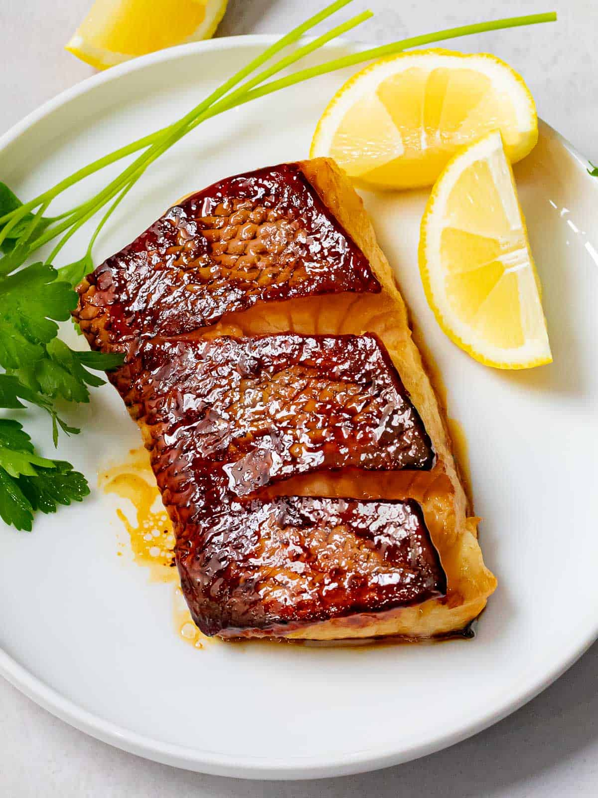 Pan seared sea bass with crispy, golden brown skin on a white plate with lemon wedges and parsley.
