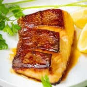 Japanese style sea bass marinated in ginger teriyaki sauce with crispy skin on a white plate next to lemons and herbs.