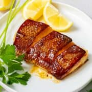 Sea bass with crispy skin marinated in Japanese teriyaki style marinade on a white plate with lemons.
