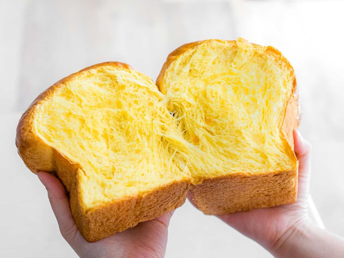 Hands pulling apart a loaf of sourdough pumpkin bread to reveal soft interior crumb.