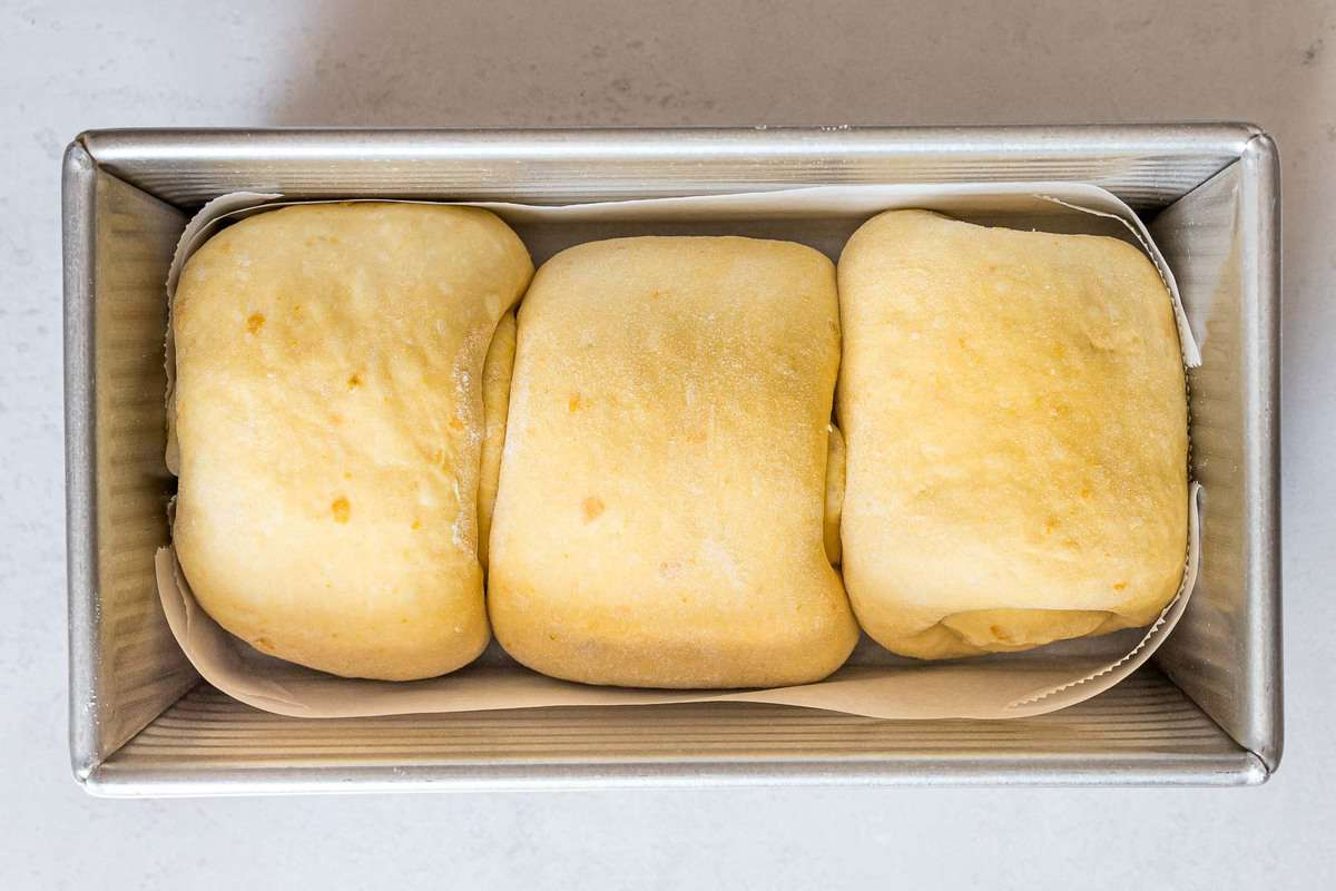 Three rolls of pumpkin sourdough bread in a loaf pan lined with parchment paper.