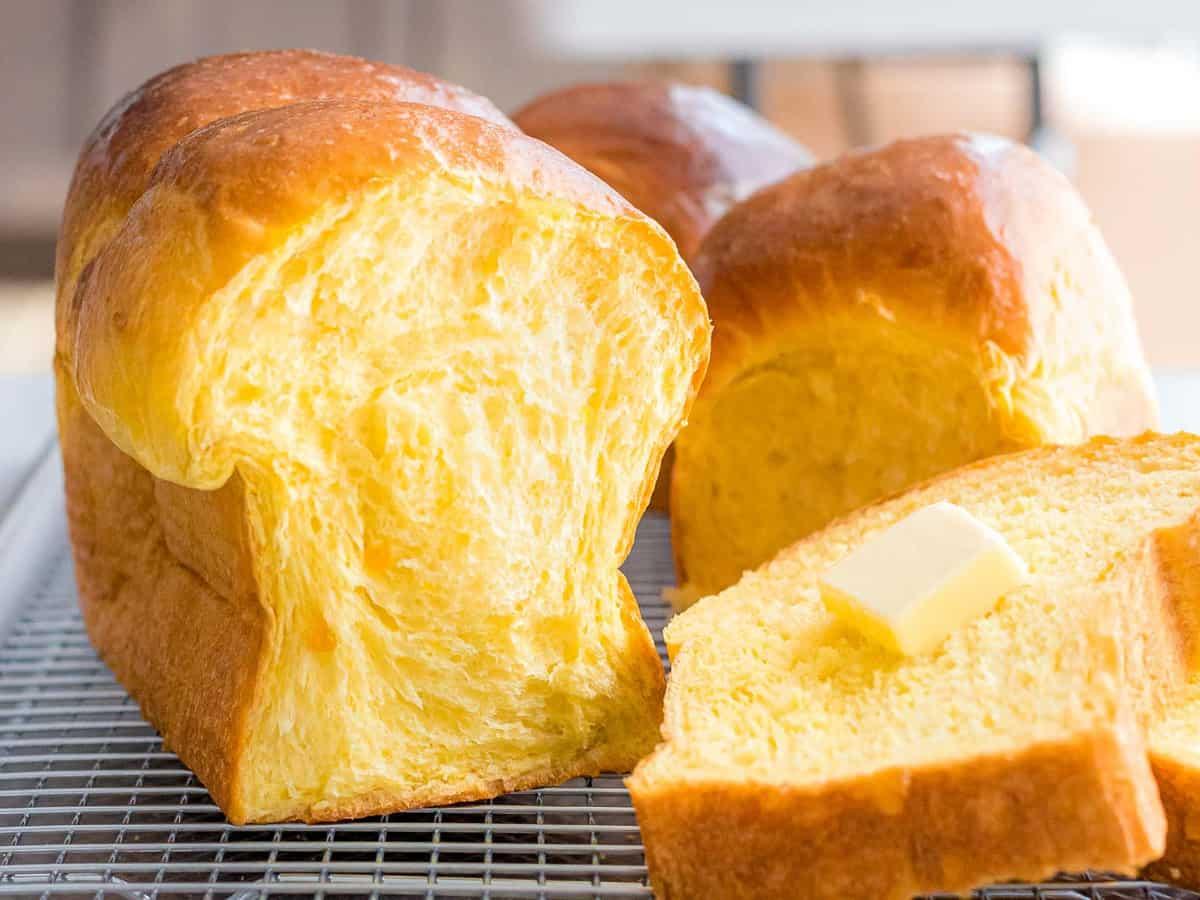 Soft, fluffy sourdough pumpkin bread sliced open with a pad of butter.