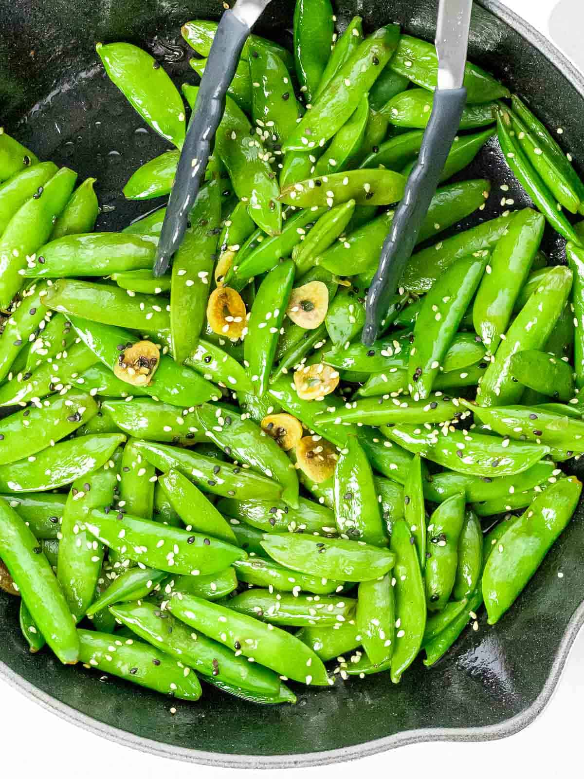 Stir fried sesame sugar snap peas with slices of garlic in a pan with a pair of tongs.