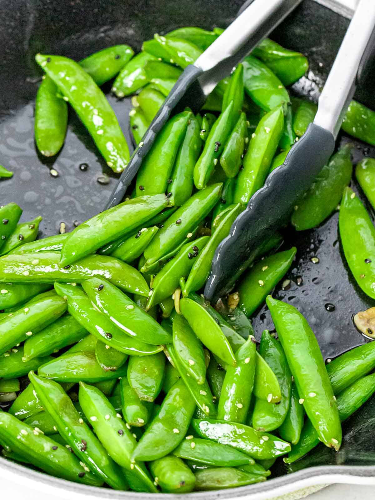 Garlic sesame sugar snap peas stir fried in a dark pan with a pair of tongs.