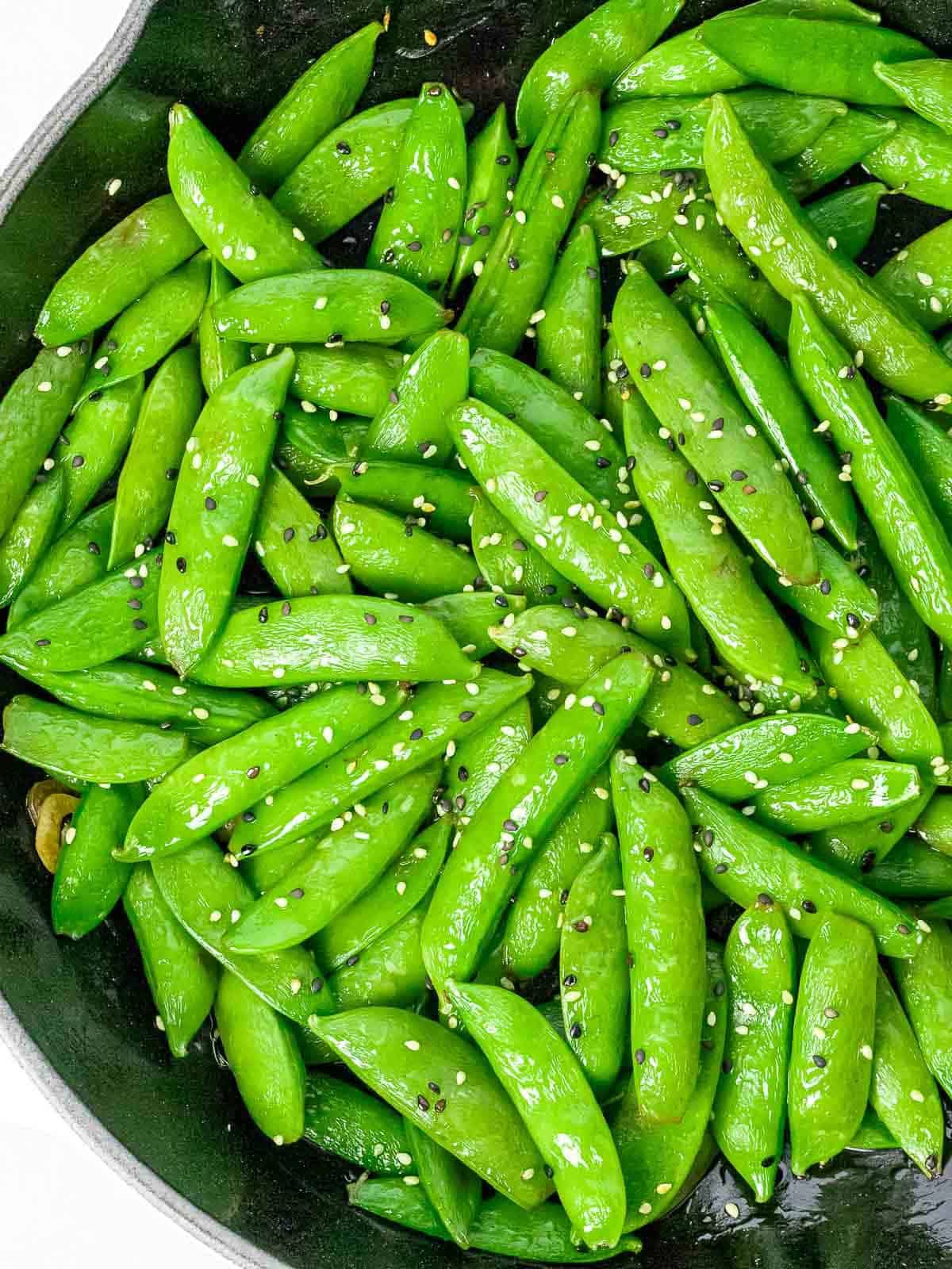 Asian style sugar snap peas stir fried with garlic and sesame in a dark pan.