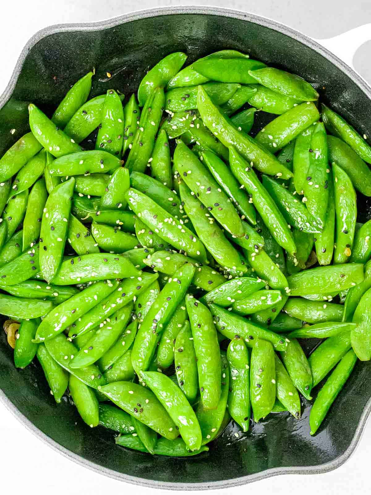 Asian style sugar snap peas with garlic and black and white sesame seeds in a dark pan.
