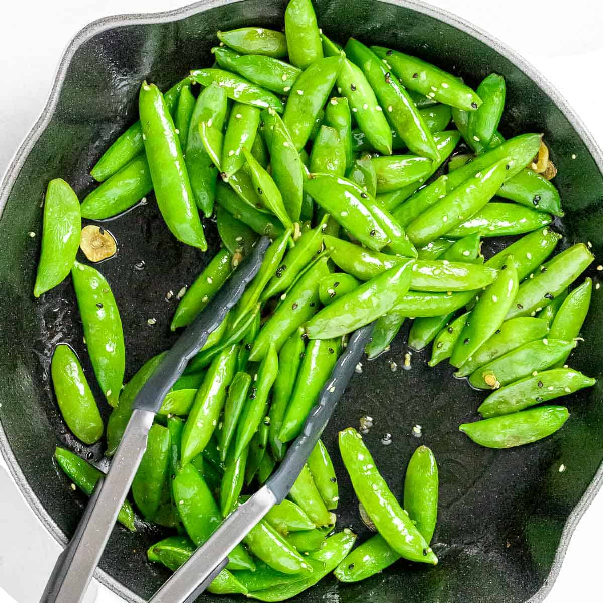 Stir fried sugar snap peas with garlic, black and white sesame seeds, and soy sauce in a dark pan with tongs.