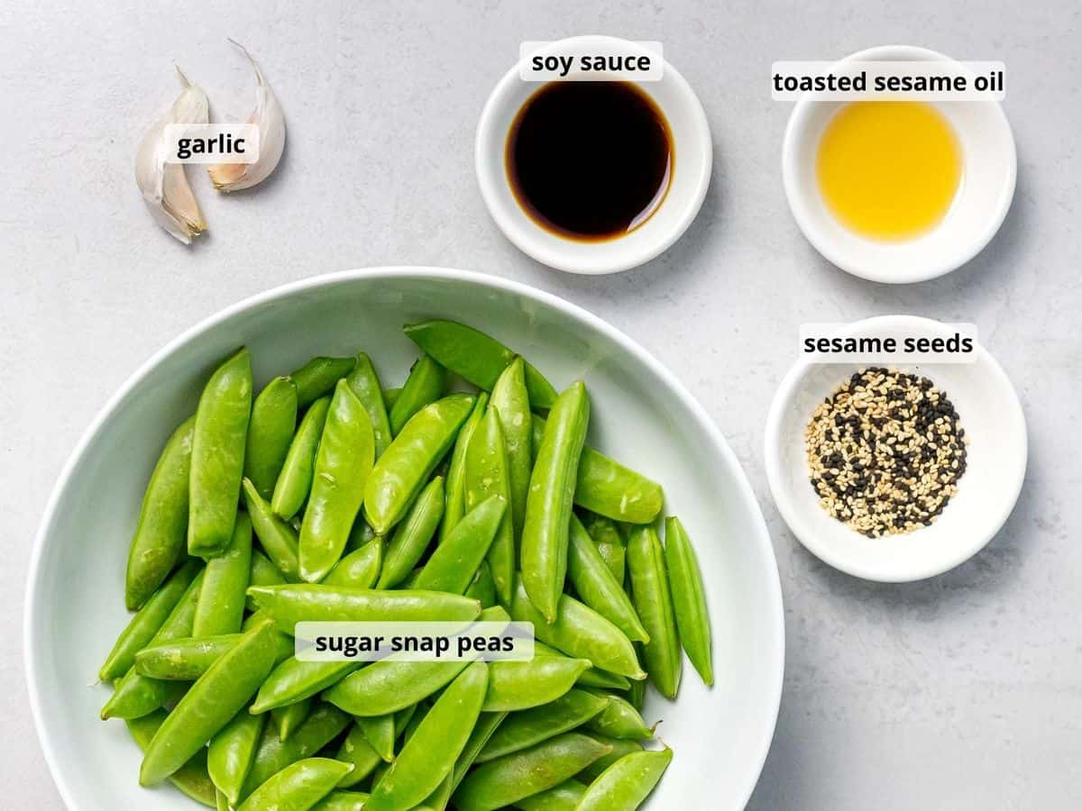 Labeled ingredients for stir fried sugar snap peas with text overlay, including sesame seeds, soy sauce, and sesame oil in small white bowls.